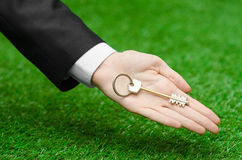 Buying a new house or land and business topic: hand in a black suit holding a key to the new house on the background of green gras. S studio Stock Photography