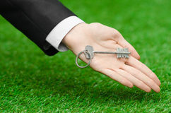 Buying a new house or land and business topic: hand in a black suit holding a key to the new house on the background of green gras. S studio royalty free stock photos