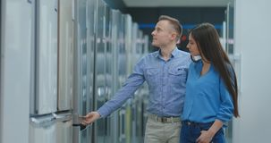 Buying a new refrigerator. Choosing the right model for a family couple in an electronics store. Buying a new refrigerator. Choosing the right model for a stock video footage