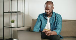 Buying Online on Laptop. Smart afro-american man dressed in denim shirt using credit card for online ordering on laptop in stylish apartment stock video