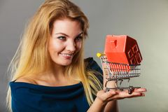 Woman holding shopping cart with house inside royalty free stock photo
