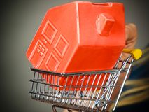 Woman hand holding shopping cart with house inside royalty free stock photos