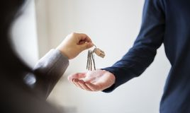 Buying real estate concept handing house keys Stock Image