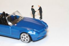 Buying and selling a car in miniature Stock Image