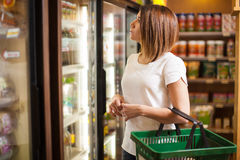 Buying some cold drinks at a grocery store. Beautiful young brunette doing some shopping at a supermarket and looking at a refrigerator Stock Images