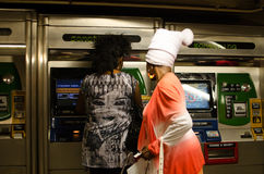 Buying subway tickets in New York. Two colorfully attired women puzzle over how to purchase their subway tickets for the New York subway Royalty Free Stock Images