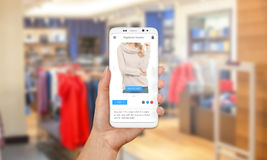 Buying sweaters and clothing online with modern mobile phone stock photography