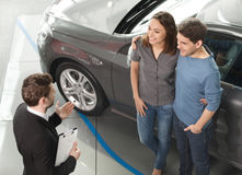 Buying their first car together. High angle view of young car sa Royalty Free Stock Photography
