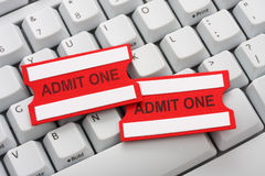 Buying tickets online. Two red and white admit one tickets on a computer keyboard Stock Photography