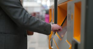 Buying a Train Ticket. Side view of an unrecognisable person using a ticket machine to buy a ticket for the train stock video footage