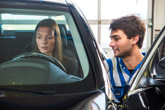 Buying a used car. Young woman, behind the wheel of a second hand car, being assisted by a service mechanic, at a used car center Royalty Free Stock Photos