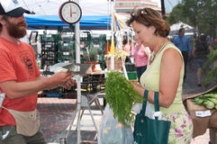 Buying Veggies from Farmer at Farmer's Market. A customer purchases vegetables from a farmer at a weekly farmer's market at Monument Square on Congress Street in Royalty Free Stock Images
