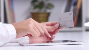 Buying on a virtual shop online with a tablet and a credit card. Close up stock footage