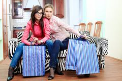 Buyings. Portrait of young women sitting at home with bags after shopping royalty free stock photography