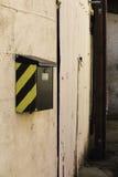 Buzón con un galón en una pared exterior Imágenes de archivo libres de regalías