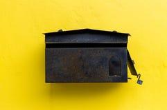 Buzón de Brown en la pared amarilla Imágenes de archivo libres de regalías