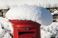 Buzón de correos británico rojo en nieve Imagenes de archivo