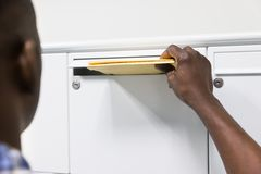 Buzón de correos de Person Hands Putting Envelope In foto de archivo