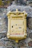 Buzón francés amarillo en la pared de piedra Fotografía de archivo