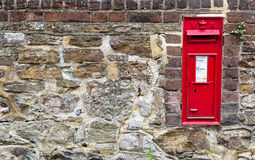 Buzón rojo hermoso incorporado a una pared de piedra Imagen de archivo