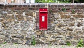 Buzón rojo hermoso incorporado a una pared de piedra Foto de archivo libre de regalías