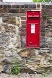 Buzón rojo hermoso incorporado a una pared de piedra Fotos de archivo libres de regalías