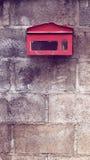 Buzón rojo viejo en el muro de cemento Foto de archivo