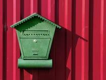Buzón verde en una cerca roja del metal fuera de la ciudad en la cabaña fotografía de archivo