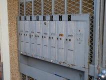 Buzones al aire libre del apartamento con la mirada oxidada y las unidades sucias 1 a 8 del estado fotos de archivo libres de regalías