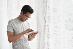 Buzy teenager asiatico con la sua compressa nella sua casa Fotografia Stock Libera da Diritti