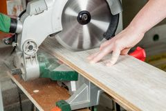 Buzz saw in action. A buzz saw is sawing a piece of laminate royalty free stock images