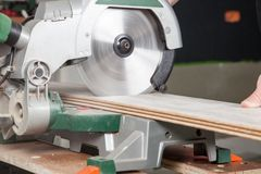 Buzz Saw in action. A buzz saw is sawing two pieces of laminate at the same time stock photography