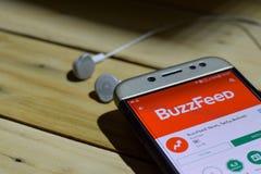 BuzzFeed: Nyheterna smaklig frågesportapplikation på den Smartphone skärmen royaltyfria foton