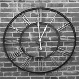 BW Clock. Black and white image of a clock with Roman numbers against a brick wall Stock Photos