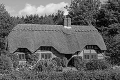 BW Cottage in New Forest 1. Lovely black and white picture postcard quintessentially English thatched cottage in the New Forest in the UK on a sunny day. Picture Stock Photography