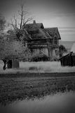 BW Frontier Farmhouse in Wheat Field. A BW of an old abandoned desolate frontier farmhouse, dead trees sitting in middle of wheat fields. Shallow depth of field Royalty Free Stock Photos