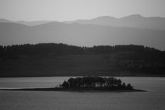 Bw lake background. Black and white landscape with small spooky island in the lake Stock Photo