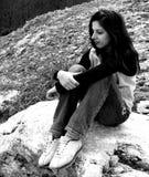 Bw-Mädchen, das auf dem Felsen sitzt lizenzfreies stockbild