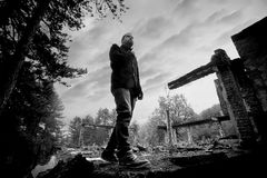 Bw man in forest ruins Royalty Free Stock Photography