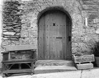 BW Old Spanish Door. Black and white image of a classic old wooden door in the Pyrenees in Spain, with a bench and flower pot either side Royalty Free Stock Image