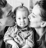 BW portrait of mother and father kissing his year-old daughter. BW portrait of lovely family together at home. Mother and father kissing his year-old daughter Royalty Free Stock Image