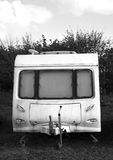 BW Rundown dirty old caravan. Black and white rundown dirty old caravan on a sunny day with clouds in the sky. Space for text Royalty Free Stock Photography