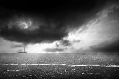 Bw seascape. Black and white dramatic sunset over the sea with lonnely boat Stock Photography