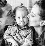BW stående av modern och fadern som kysser hans åriga dotter Royaltyfri Bild