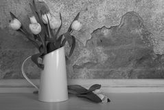 BW White tulips in jug. Black and white image of white tulips in a white jug on a table with a textured background and space for text Stock Photos