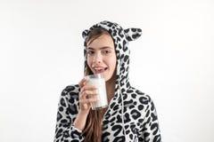 Być może szkło mleko i Młoda ładna kobieta trzyma szkło mleko w łaciastej krowy piżamie urocza dziewczyna zdjęcie royalty free