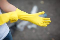 Być ubranym lateksową rękawiczkę dla czyścić na ręce na asfaltowym tle Banialuki na tylnej stronie Zdjęcia Stock