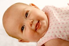 Byby Smile. A baby girl lying on her back smiling to the camera stock photos