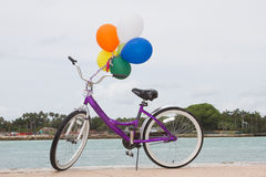 Bycicle and Balloons. Purple Bycicle with 6 balloons attached Stock Image