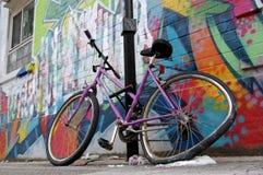 Bycicle danificado estacionado parede da roda dos grafittis da rua Fotos de Stock